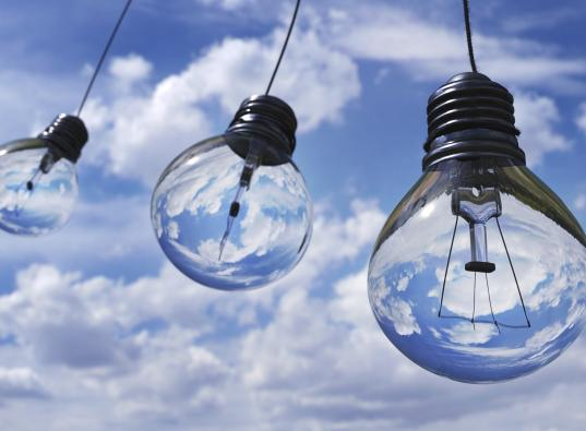 Three hanging light bulbs with blue sky background